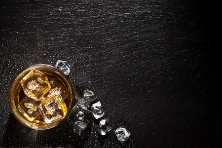 Photo pour Glass of whiskey with ice on black stone table. Top view with copy space - image libre de droit