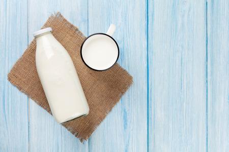 Photo pour Milk cup and bottle on blue wooden table. Top view with copy space - image libre de droit