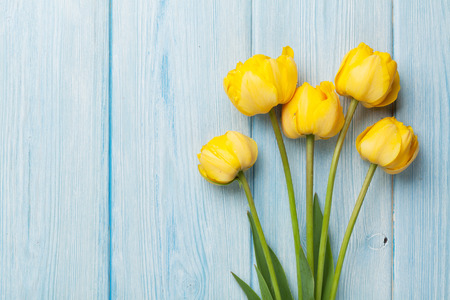 Foto de Yellow tulips over wooden table background with copy space - Imagen libre de derechos
