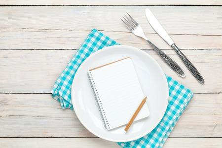 Foto de Notepad for recipe over empty plate and silverware on white wooden table background - Imagen libre de derechos