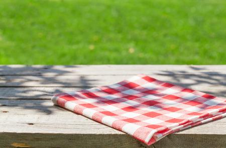 Foto de Empty wooden garden table with tablecloth with green bokeh background - Imagen libre de derechos