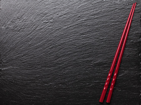Photo for Japanese sushi chopsticks on black stone background. Top view with copy space - Royalty Free Image