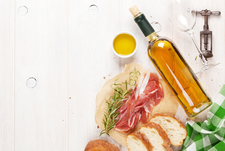 Photo for Prosciutto, wine, ciabatta, parmesan and olive oil on wooden table. Top view with copy space - Royalty Free Image