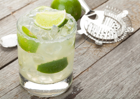 Foto de Classic margarita cocktail with salty rim on wooden table with limes and drink utensils - Imagen libre de derechos