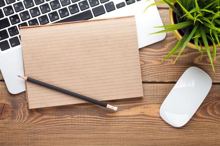 Foto de Office desk table with computer, supplies and grass. Top view with copy space - Imagen libre de derechos