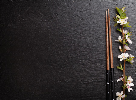 Photo for Japanese sushi chopsticks and sakura blossom on black stone background. Top view with copy space - Royalty Free Image