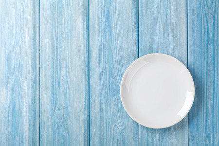 Photo pour Empty plate on blue wooden background. Top view with copy space - image libre de droit