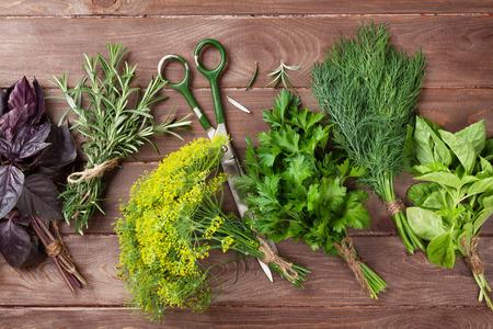 Photo pour Fresh garden herbs over wooden table. Top view - image libre de droit