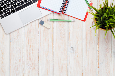 Foto de Office desk table with computer, supplies and flower. Top view with copy space - Imagen libre de derechos