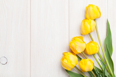 Photo for Yellow tulips over wooden table background with copy space - Royalty Free Image
