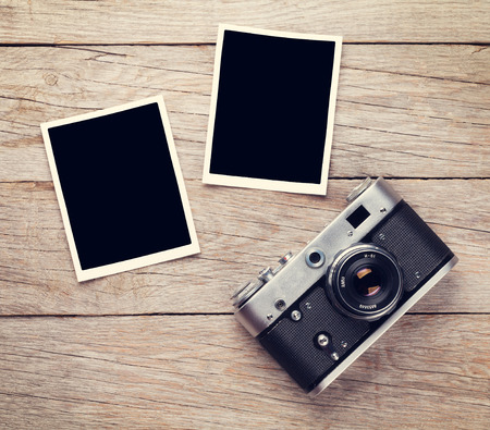 Photo for Vintage film camera and two blank photo frames on wooden table. Top view - Royalty Free Image
