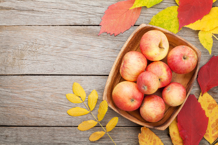 Photo for Apples in bowl and colorful autumn leaves on woden background with copy space - Royalty Free Image