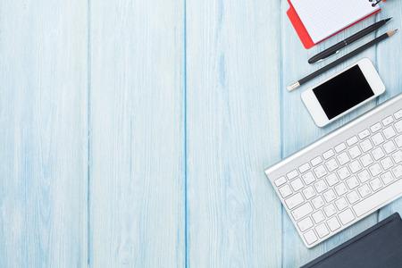 Foto de Office desk table with supplies, smartphone and computer. Top view with copy space - Imagen libre de derechos