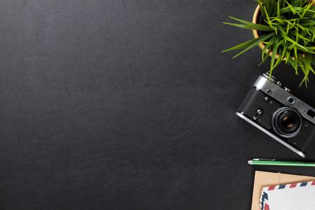 Foto de Office leather desk table with flower, camera and supplies. Top view with copy space - Imagen libre de derechos