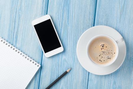Foto de Coffee cup, smartphone and blank notepad on wooden table background. Top view with copy space - Imagen libre de derechos