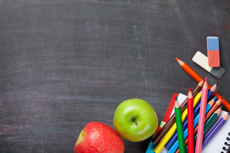 Foto de School supplies and apples on blackboard background. Top view with copy space - Imagen libre de derechos