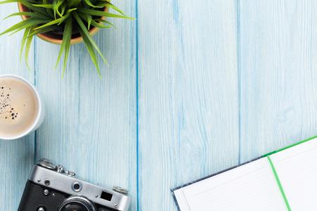 Foto de Office desk table with notepad, camera, coffee and flower. Top view with copy space - Imagen libre de derechos