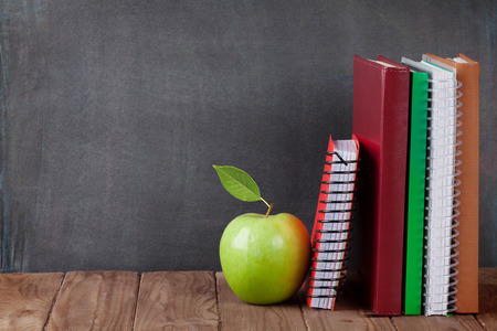 Foto de School and office supplies on classroom table in front of blackboard. View with copy space - Imagen libre de derechos