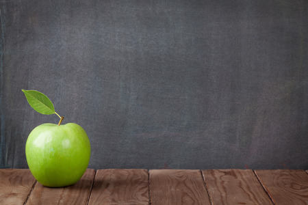 Photo for Apple fruit on classroom table in front of blackboard. View with copy space - Royalty Free Image