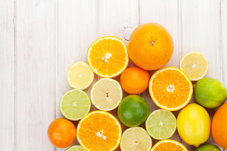 Foto de Citrus fruits. Oranges, limes and lemons. Over wooden table background with copy space - Imagen libre de derechos