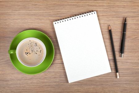 Foto de Blank notepad and coffee cup on office wooden table - Imagen libre de derechos