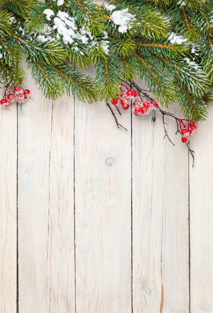 Photo pour Christmas wooden background with fir tree and holly berry. View from above with copy space - image libre de droit