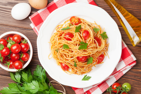 Photo for Spaghetti pasta with tomatoes and parsley on wooden table. Top view - Royalty Free Image
