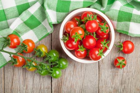 Photo pour Cherry tomatoes bowl on wooden table. Top view - image libre de droit
