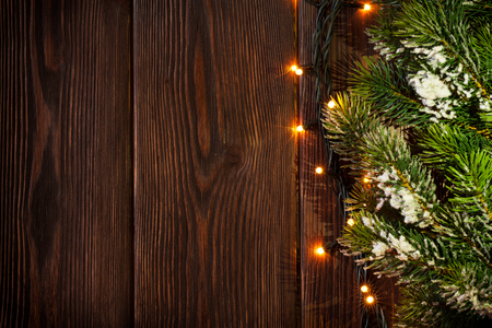 Photo for Christmas tree branch and lights on wooden background. View with copy space - Royalty Free Image