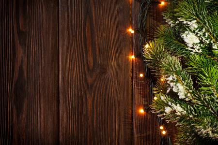 Foto de Christmas tree branch and lights on wooden background. View with copy space - Imagen libre de derechos