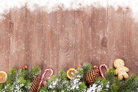 Foto de Christmas wooden background with snow fir tree and holiday decor - Imagen libre de derechos