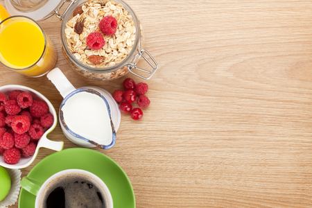 Foto de Healty breakfast with muesli, berries, orange juice, coffee and croissant. View from above on wooden table with copy space - Imagen libre de derechos