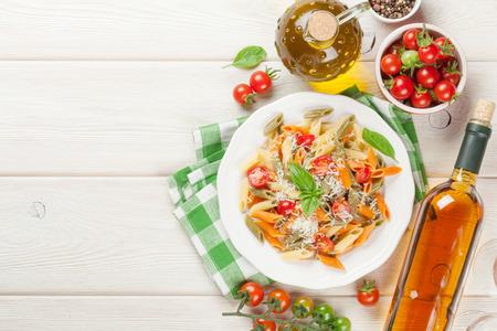 Foto de Colorful penne pasta and white wine on wooden table. Top view with copy space - Imagen libre de derechos