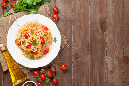 Foto de Spaghetti pasta with tomatoes and parsley on wooden table. Top view with copy space - Imagen libre de derechos