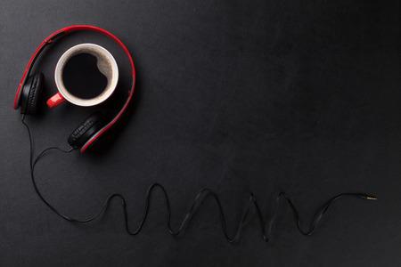 Foto de Headphones and coffee cup on black leather desk table. Music concept. Top view with copy space - Imagen libre de derechos