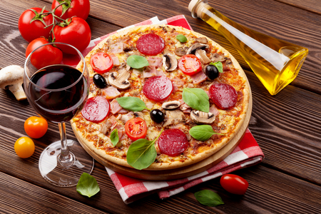 Photo pour Italian pizza with pepperoni, tomatoes, olives, basil and red wine on wooden table. Top view - image libre de droit