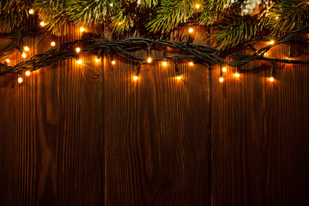 Foto de Christmas tree branch and lights on wooden background. View with copy space - Imagen libre de derechos