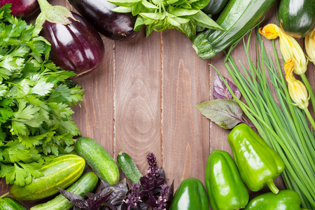 Foto per Fresh farmers garden vegetables and herbs on wooden table. Top view with copy space - Immagine Royalty Free
