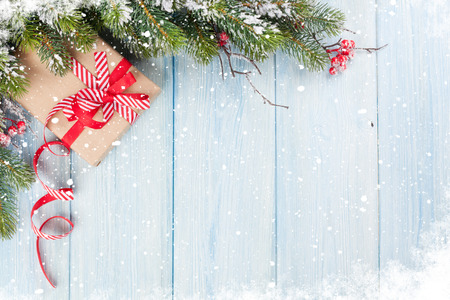 Photo pour Christmas wooden background with snow fir tree and gift box. View with copy space - image libre de droit