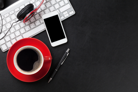 Foto de Office leather desk table with coffee cup, computer, smartphone and headphones. Top view with copy space - Imagen libre de derechos