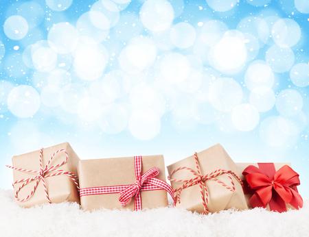 Foto de Christmas gift boxes in snow with bokeh background for copy space - Imagen libre de derechos