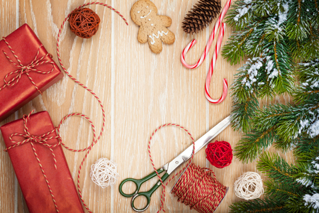 Foto de Christmas presents wrapping and snow fir tree over wooden table background with copy space - Imagen libre de derechos