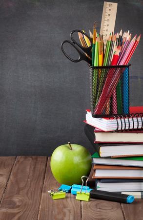 Foto de School and office supplies and apple on classroom table in front of blackboard. View with copy space - Imagen libre de derechos