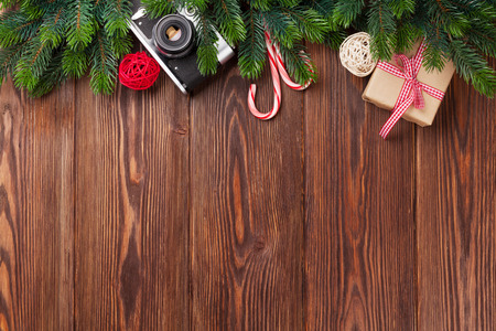Photo pour Christmas tree branch, gift box and camera on wooden table. Top view with copy space - image libre de droit