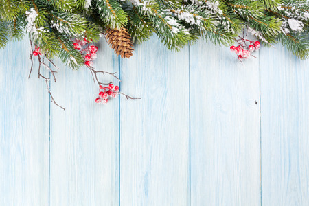 Photo pour Christmas wooden background with snow fir tree and holly berry - image libre de droit