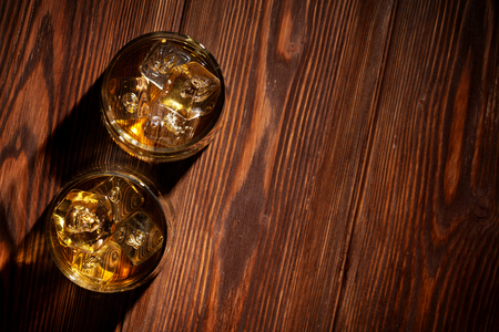 Photo pour Glasses of whiskey with ice on wooden table. Top view with copy space - image libre de droit