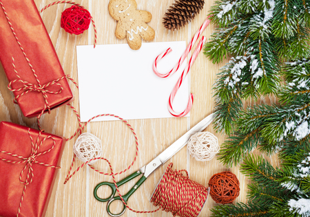 Foto de Christmas presents wrapping and snow fir tree over wooden table background with blank greeting card - Imagen libre de derechos