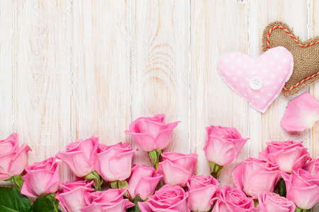 Photo pour Valentines day card with pink roses and handmaded toy hearts over wooden table. Top view with copy space - image libre de droit