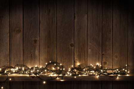 Photo for Christmas lights on shelf in front of wooden wall with copy space - Royalty Free Image