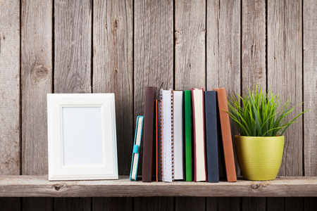 Photo for Wooden shelf with photo frames, books and plant in front of wooden wall. View with copy space - Royalty Free Image